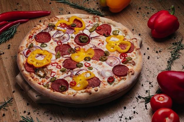 Hele rustieke pizza met salami jachtworst jalapeno peper uienringen geserveerd op houten bord