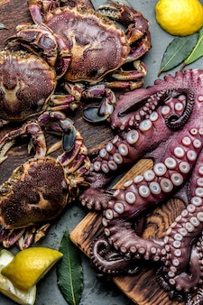 Hele verse rauwe octopus en krabben op een houten bord met citroen en laurier