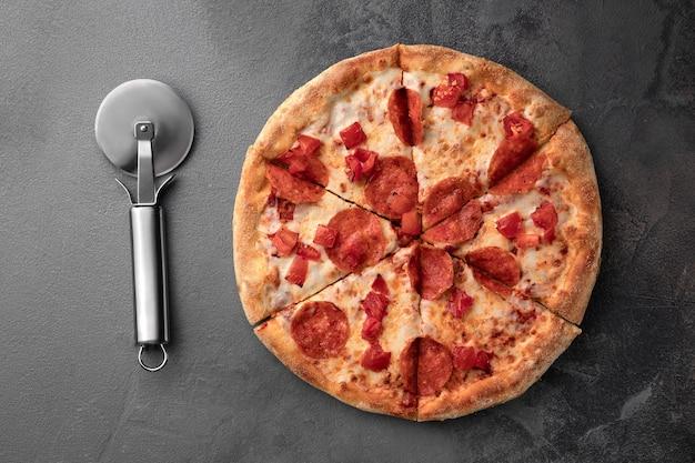 Hele verse ronde pizza met pepperoni en mozzarellakaas en mes op een grijze tafelblad-weergave.