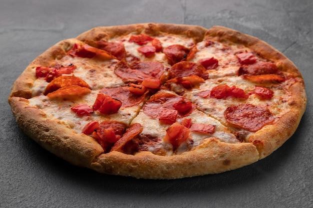 Hele verse ronde pizza met pepperoni en mozzarellakaas op een grijze tafel.