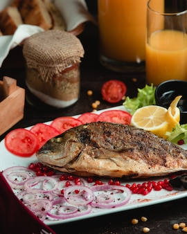 Hele vis gegrild en geserveerd met tomaat, citroen en ui.