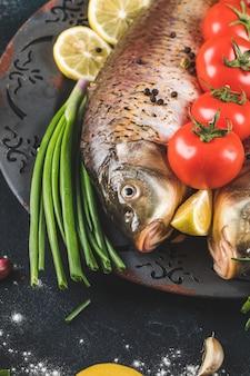 Hele vis met kruiden, tomaat en schijfjes citroen