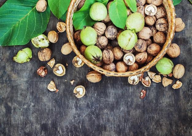 Hele walnoten en gewist in de mand zwarte houten achtergrond bovenaanzicht gezond concept