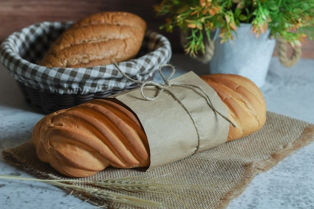 Hele zelfgebakken brood vastgebonden met touw op stenen oppervlak.