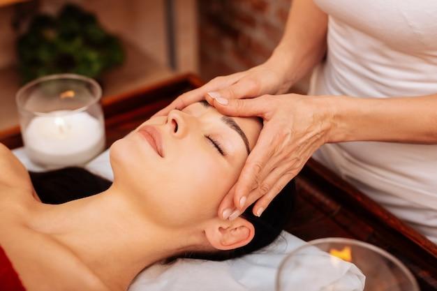 Helemaal comfortabel. ervaren masseuse in wit t-shirt die een ontspannende massage voor het gezicht maakt terwijl de vrouw op een houten tafel ligt