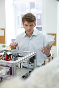 Helemaal gefocust. jonge kantoormedewerker die zich concentreert op het 3d-printerproces, terwijl hij leert hoe hij een nieuw apparaat moet bedienen