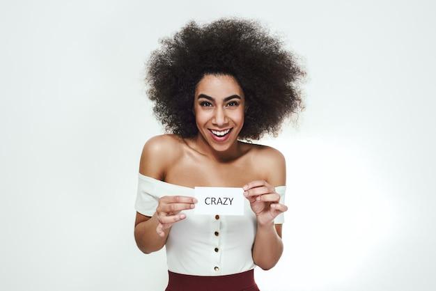 Helemaal gekke speelse jonge afrikaanse vrouw die lacht en een stuk papier vasthoudt dat is