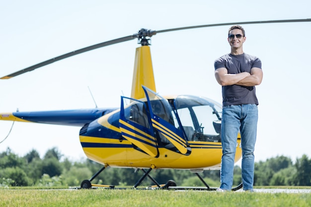 Helemaal klaar voor de missie. charmante atletische luchtpolitieagent die zijn armen over zijn borst vouwt en voor een helikopter poseert