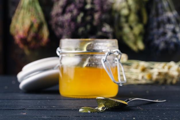 Helende honing met geneeskundekruiden op donkere muur