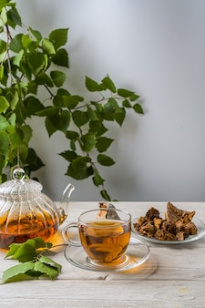 Helende infusie van berkenzwam met chaga-stukjes in een kom. chaga-paddenstoelenkoffie of -thee.