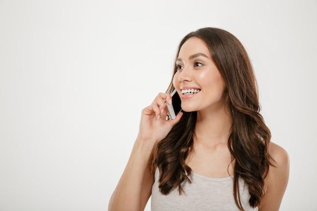Helft-draai portret van kaukasische vrouw die met lang bruin haar terwijl het hebben van prettig mobiel gesprek op haar smartphone, over witte muur glimlacht
