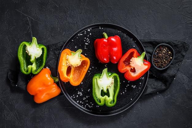 Helften gesneden oranje, groene en rode paprika. zwarte achtergrond. bovenaanzicht