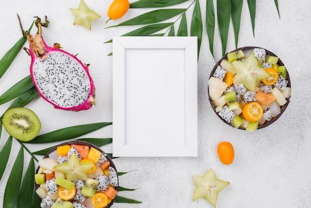 Helften van kokos gevuld met fruitsalade en frame