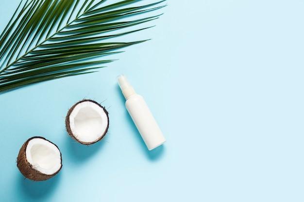 Helften van kokos, palmblad en spuitfles op een blauw