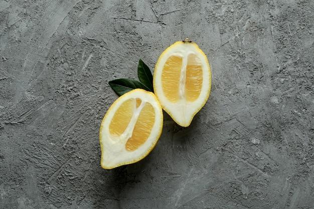 Helften van rijpe citroen op grijs