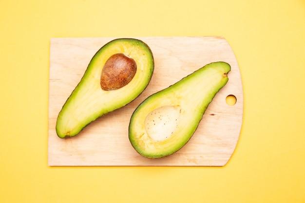 Helften van verse avocado geplaatst op snijplank