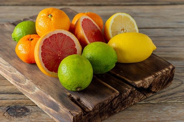 Helften van verse citrusvruchten op houten achtergrond. sinaasappel, grapefruit, limoen, citroen, mandarijn snijringen