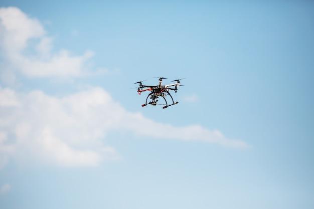 Helikopter met een professionele camera vliegt over de bomen tegen een blauwe hemel. dron.