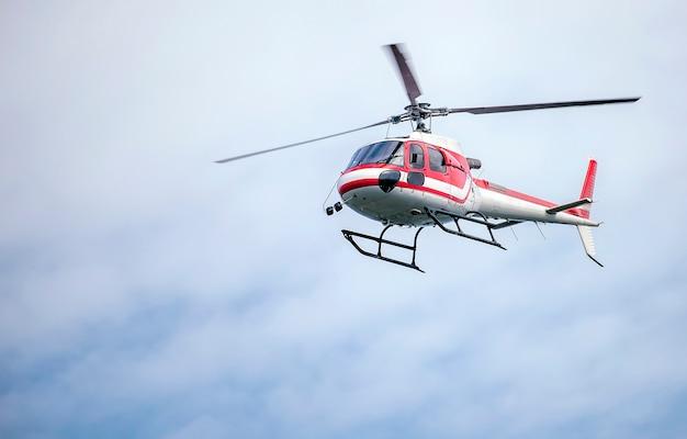 Helikopter met rode en witte kleur vliegen in de lucht