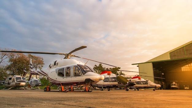Helikopter op het parkeerterrein of de baan die op onderhoud met zonsopgangachtergrond wachten