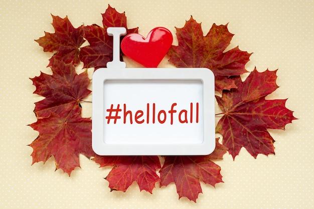Hellofall-tekst in frame met rode esdoornbladeren op pastelgele achtergrond