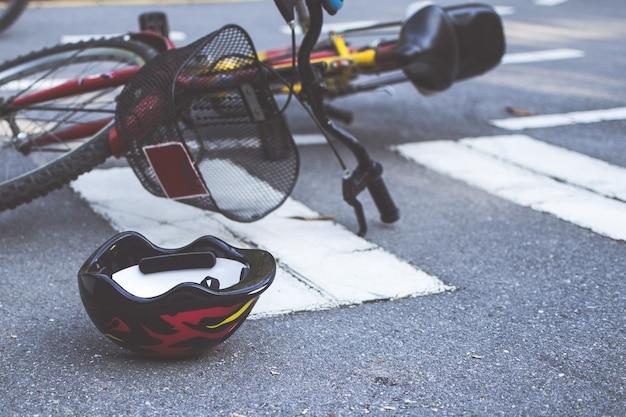 Helm en fiets die na een ongeval op een oversteekplaats voor voetgangers op de weg liggen