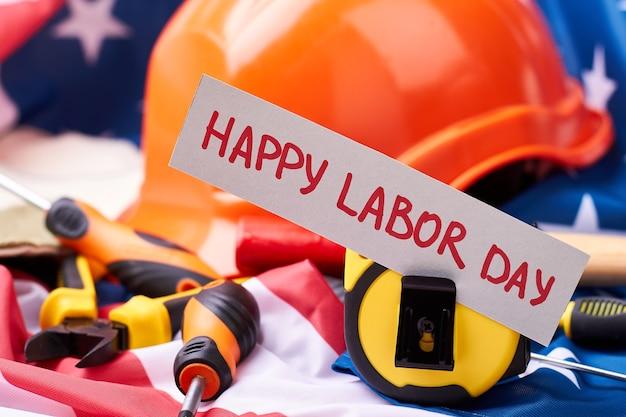 Helm in de buurt van labor day-kaart. amerikaanse vlag en hulpmiddelen. succes begint met hard werken.