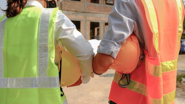 Helm in de hand, ingenieur aannemersteam dat werkveiligheidsplan industrieproject ontmoet en ontwerp controleert op de bouwplaats.