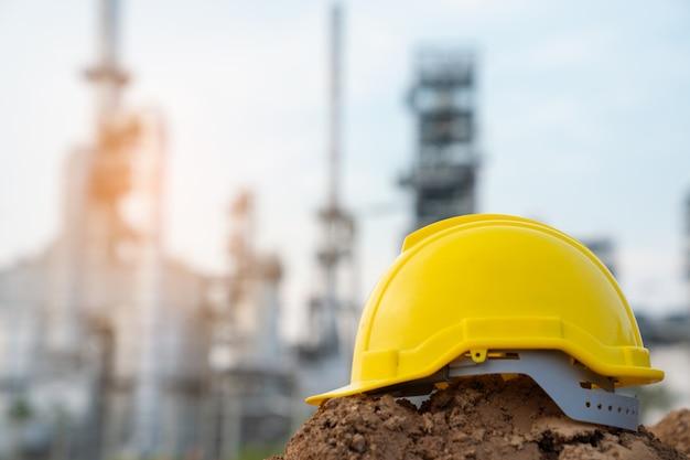 Helm van de ingenieur die van de raffinaderijindustrie ppe dragen bij raffinaderijbouwwerf