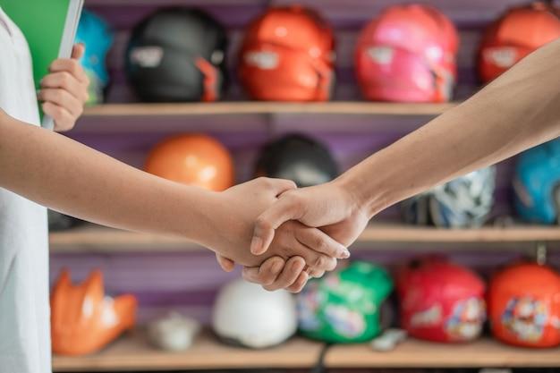 Helm verkoper schudt de hand met klant tegen helm rek achtergrond weergeven