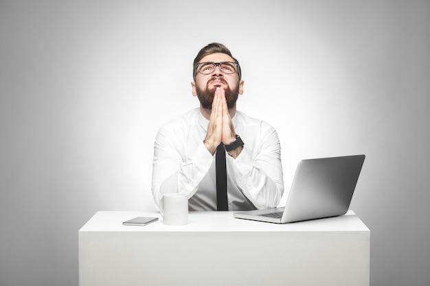 Help alstublieft! portret van een hoopvolle, bebaarde jonge manager in wit overhemd en zwarte stropdas zit op kantoor en vraagt om hulp in het universum, hand in hand zoals bidden, omhoog kijkend. studio opname, geïsoleerd