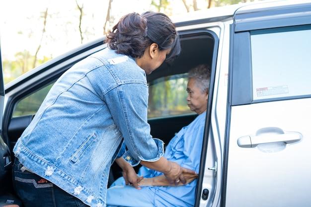 Help en steun aziatische senior of oudere oude dame vrouw patiënt naar haar auto