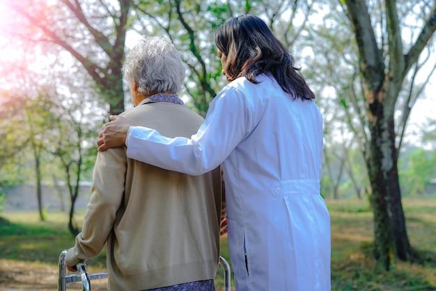 Help en zorg aziatische senior of oudere oude dame vrouw gebruik wandelaar