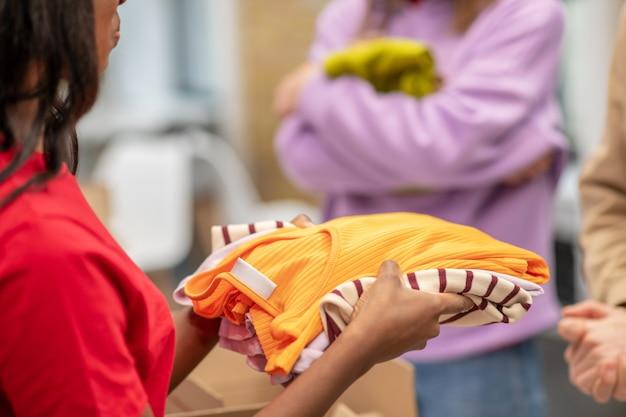 Help, kleren. meisje met een donkere huidskleur vrijwillig in een rode t-shirt die kleding aanbiedt voor mensen die een liefdadigheidsorganisatie nodig hebben