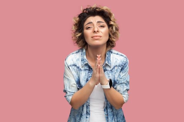 Help me alsjeblieft of vergeef me. portret van een bezorgde, droevige jonge vrouw met krullend haar in een casual shirt dat met palmhanden staat en naar de camera kijkt die tevreden smeekt. studio opname, geïsoleerd op roze achtergrond.