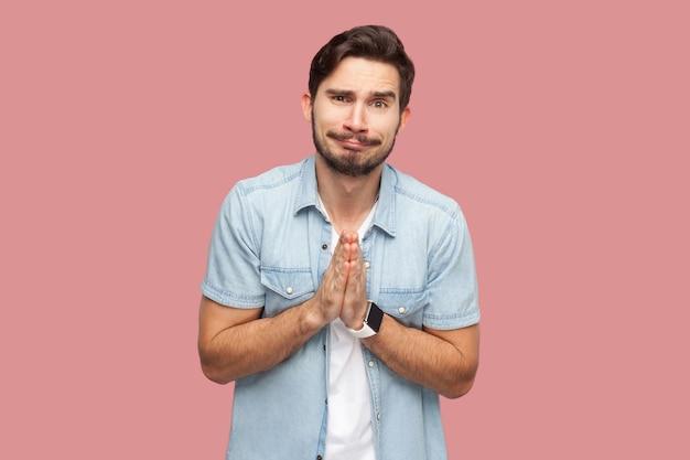 Help me alsjeblieft, of vergeef me. portret van een trieste hoopvolle knappe bebaarde jongeman in een blauw casual stijlshirt dat staat, naar de camera kijkt en smeekt. indoor studio opname, geïsoleerd op roze achtergrond.