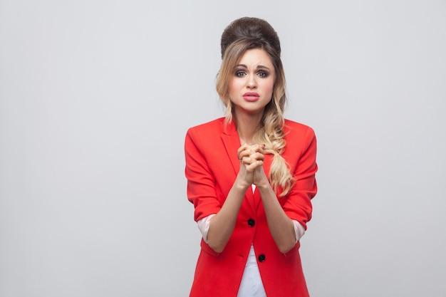 Help me alstublieft. bezorgde mooie zakenvrouw met kapsel en make-up in rode mooie blazer, staande met palmhanden en vragend om te vergeven of te helpen. indoor studio opname, geïsoleerd op een grijze achtergrond.