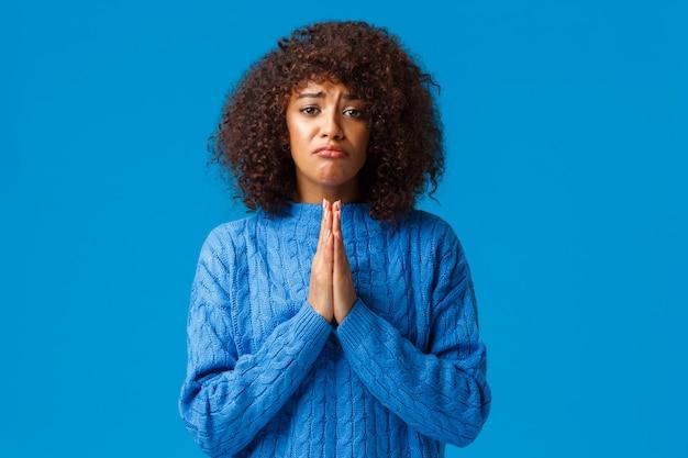 Help me alstublieft. mokkend sombere schattige afro-amerikaanse vriendin met afro kapsel, druk de handen in elkaar om te bidden, smekend, excuses te vragen, sorry voor de fout, bedelend over de blauwe muur