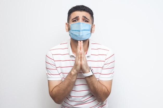 Help me alstublieft. portret van een trieste alleenstaande man met een chirurgisch medisch masker in een gestreept t-shirt, staande, palmhanden en kijkend naar de camera die smeekt of smeekt. indoor studio-opname, geïsoleerd op een witte achtergrond