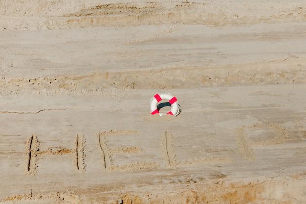 Help me de inscriptie en reddingsboei op het zand. help me alstublieft. op een tropisch strand