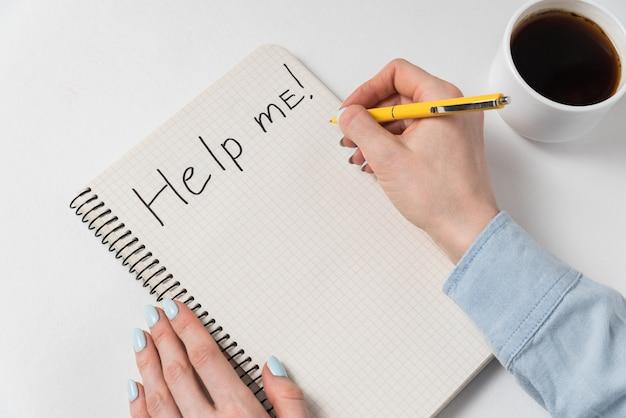 Help me op te merken in kladblok op witte achtergrond. vrouwelijke hand maken van notitie in kladblok naast kopje koffie