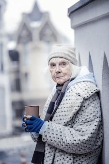 Help mij. depressieve oude vrouw die bij de muur staat terwijl ze je om geld vraagt