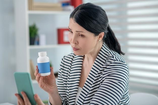 Help online. donkerharige ernstige vrouw met een smartphone en medicijnen in haar handen zorgvuldig kijken naar het scherm online raadplegen.