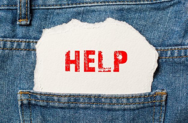 Help op wit papier in de zak van blauwe spijkerbroek