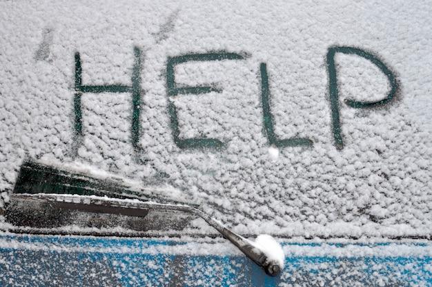 Help woord geschreven op de achterruit van de auto bedekt door sneeuwval