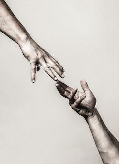 Helpende hand concept en internationale dag van vrede, ondersteuning. helpende hand uitgestrekt, geïsoleerde arm, redding. sluit omhoog hulphand. twee handen, helpende arm van een vriend, teamwork. zwart en wit.