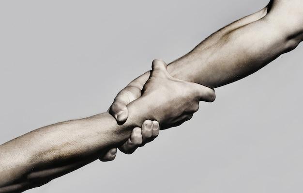 Helpende hand concept en internationale dag van vrede, ondersteuning. helpende hand uitgestrekte, geïsoleerde arm, redding. sluit omhoog hulphand. twee handen, helpende arm van een vriend, teamwork. zwart en wit.