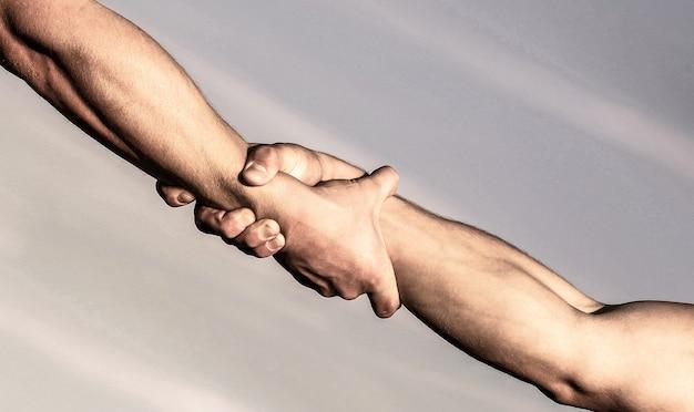 Helpende handen concept, ondersteuning. sluit omhoog hulpwapen. helpende hand concept en internationale dag van vrede, ondersteuning. twee handen, helpende arm van een vriend, teamwork.