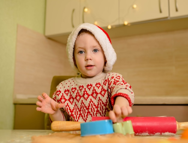 Helper in kerstmuts en rode trui die thuis koekjes maakt. kerstmis