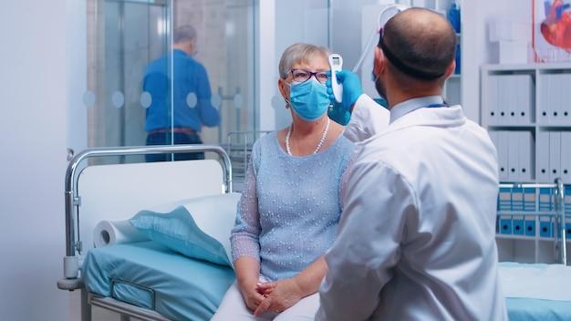 Helthcare-medewerker die de temperatuur van de oude vrouw controleert met een thermometerkanon. gepensioneerde senior gepensioneerde die een masker draagt en een gezondheidswerker in beschermende uitrusting voor overleg. covid 19 consultatie